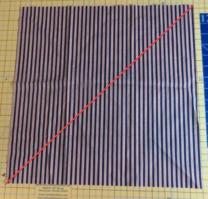 Photo of fabric with red line going from corner to corner to illustrate where to cut to make triangles